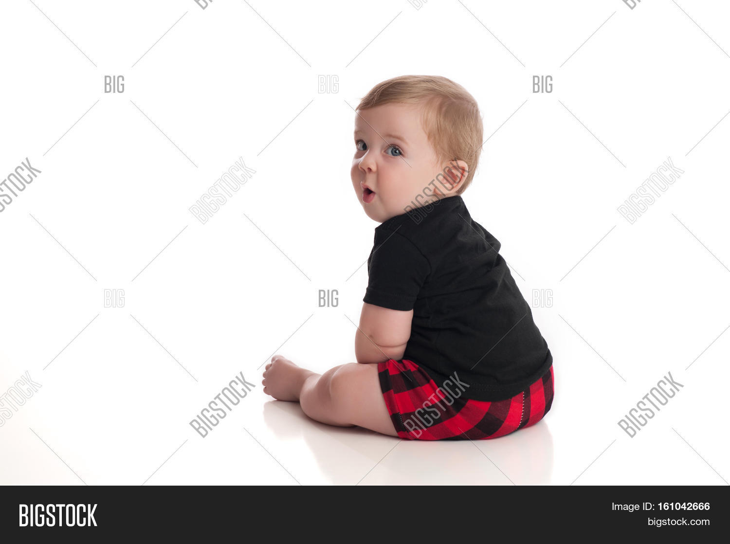 An eight month old baby boy sitting on a white seamless background he is looking