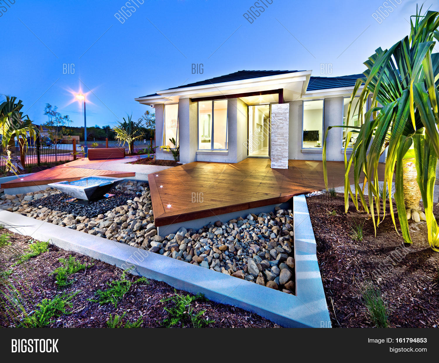 Modern mansion at night with lights on over the gravel garden with a pond near