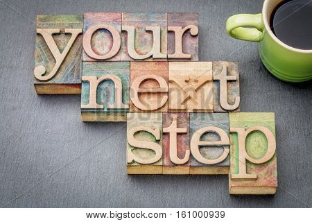 your next step word abstract in wooden letterpress printing blocks with a cup of coffee