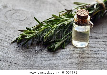 Rosemary essential oil in a glass bottle with fresh green rosemary herb on old wooden table. Rosemary oil for spa, aromatherapy and body care. Extract oil of rosemary. Selective focus.
