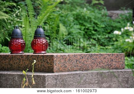 horizontal view on two red cemetery lanterns on grave granite slab with leaves and fern at the Lychakiv cemetery in Lviv. symbol of death, sorrow, short life, memory