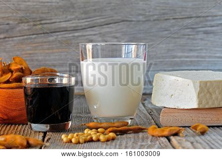 Glass of soybean milk sauce and tofu on a wooden table