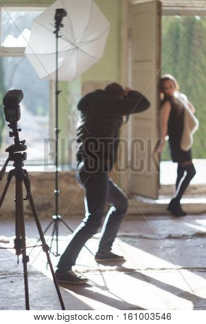 Photographer and model during photosession, photoshooting background