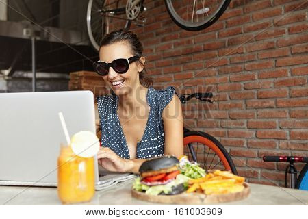 Cheerful Young Lady In Shades Sitting In Front Of Laptop Computer, Looking At Screen And Smiling Whi