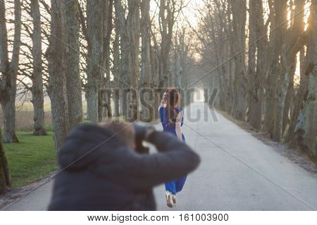 Photographer in motion, doing a photo shoot at a model. Focus on model