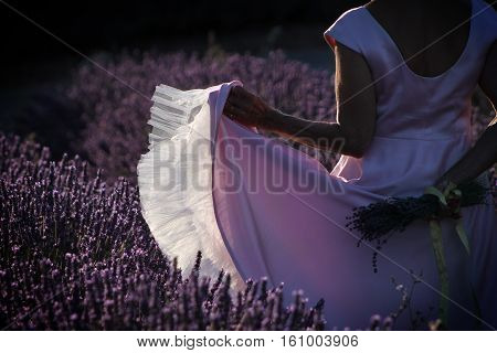 A woman in a pink dress with ruffles dancing in a lavender field.