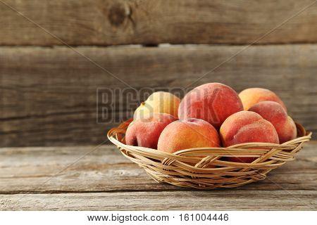 Sweet Peach Fruit In Basket On Grey Wooden Table