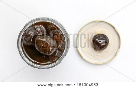 picture of an open jar of preserved figs on white background