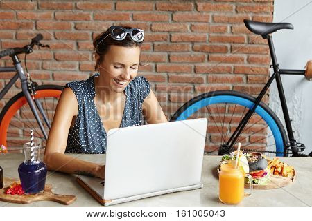 Beautiful Woman With Joyful Smile Wearing Sunglasses On Her Head Browsing Internet On Laptop, Checki