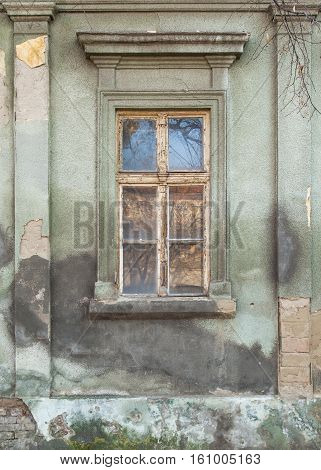 dilapidated window on the old hobbled home
