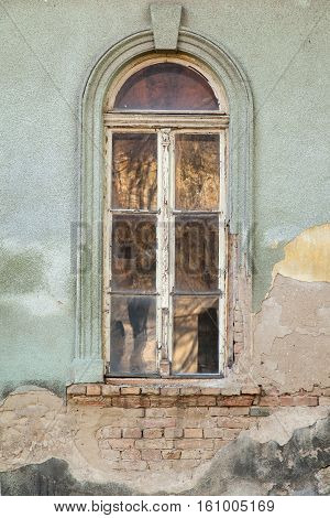 High wooden window on the dilapidated wall of the house