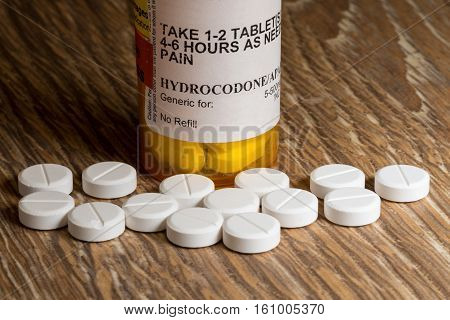 Close photo of prescription bottle for Hydrocodone tablets and pills on wooden table for opioid epidemic illustration