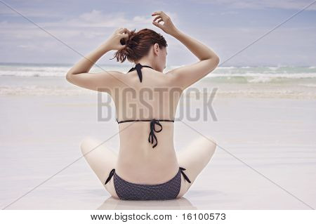 Girl Sitting On Beach.