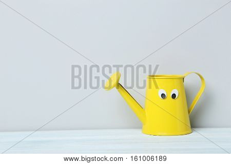 Yellow Watering Can With Googly Eyes On A Grey Background