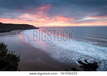Sunrise at Caswell Bay, one of the most popular and easily accessible beaches on the Gower peninsula in Swansea