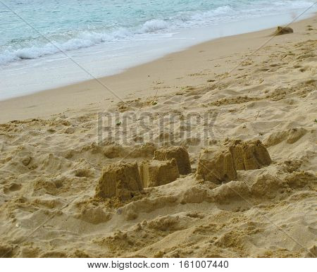 A sandcastle on a beautiful white sand beach in summer