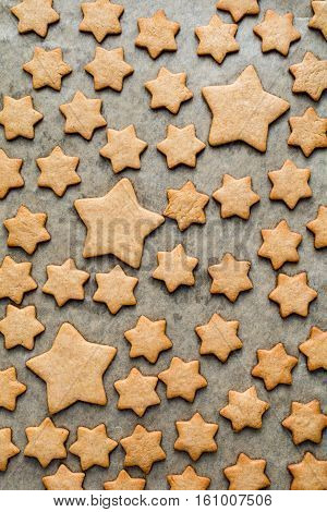 Pattern of stars shaped cookies on parchment paper background. Christmas, New Year, holidays concept. Vertical composition, top view