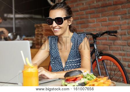 Cheerful Female In Trendy Sunglasses Communicating With Friend Online, Using Free Wireless Internet