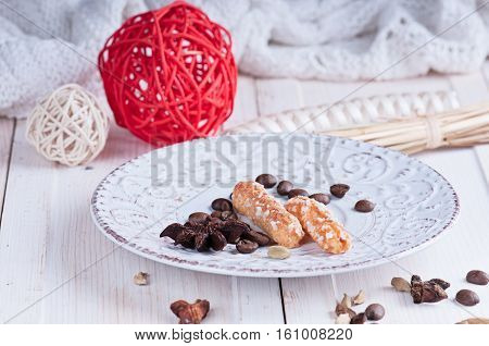 a sugar cookies on a vintage saucer with ornament balls and spice anisetree and cardamom on a white surface and a knitted blanket in the background.