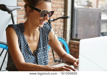Beautiful Female With Happy Smile Messaging Friends Online Via Social Networks, Using Wireless Inter