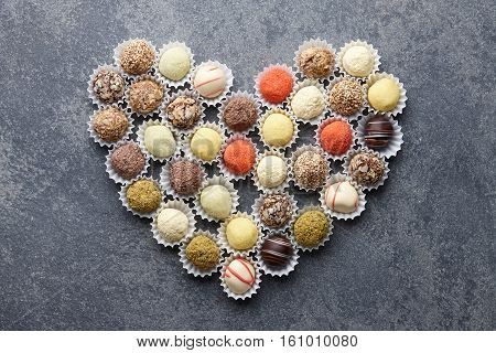 Chocolate truffle candies arranged in a heart shape on gray stone background
