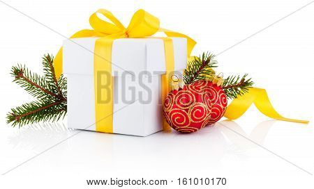 White gift box tied yellow ribbon pine tree branch and christmas baubles Isolated on white background