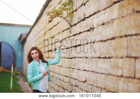 Young Pretty Cheerful Girl Standing Near Stone Walls And Delight Shows On Top Of Fence, Where A Youn