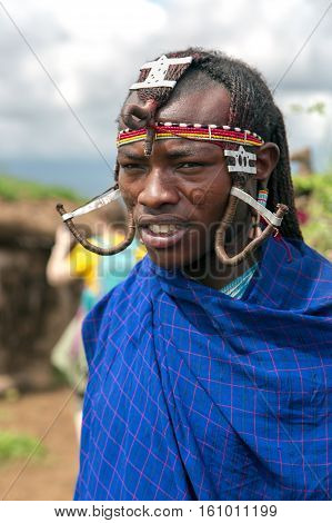 AFRICA, KENYA, MAY, 5, 2016 - Portrait of  warrior Maasai Mara tribe with traditional headdress and jewelry from beads and braids in Kenya, Africa