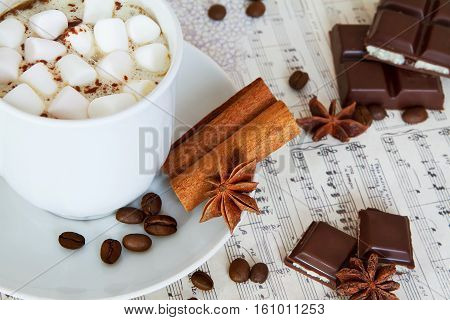Marshmallow cup of coffee and pices of chocolate.Some coffee beans on the background