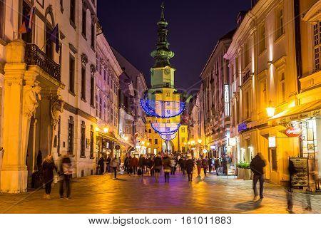 BRATISLAVA SLOVAKIA - 4TH DECEMBER 2016: Stara radnica and Bratislava Christmas Market at night. The Blur of people can be seen.