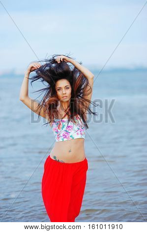 Portrait Of Beautiful Slim Woman, Dressed In A T-shirt And Red Skirt At The Hips, With Piercings In