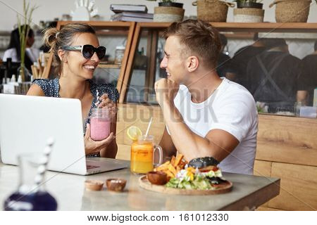 Happy Couple Having Lunch Together At Cozy Cafeteria, Sitting In Front Of Laptop Computer. Pretty Wo