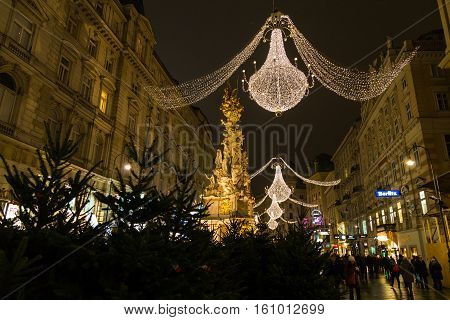 VIENNA AUSTRIA - 2ND DECEMBER 2015: A view along Graben Street at night during the Christmas season. People decorations and buildings can be seen. The Pestsaule memorial column can be seen.