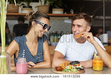 Love And Friendship. Happy Couple Eating Burger With French Fries And Having Fresh Drinks During Dat