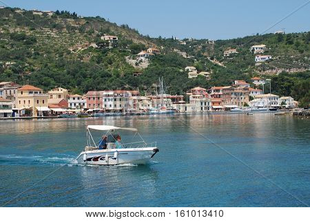 PAXOS, GREECE - JUNE 12, 2014: A small boat departs Gaios harbour on the Greek island of Paxos. Gaios is the Capital of the 13km long Ionian island.