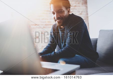 Cheerful bearded African man working on laptop while sitting sofa at his modern office place.Concept of young people using mobile devices.Brick wall blurred background.Horizontal, flares