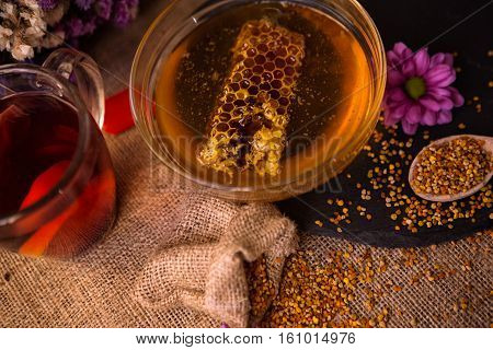 Still life of healthy cup of tea honey honeycombs wax and pollen granule