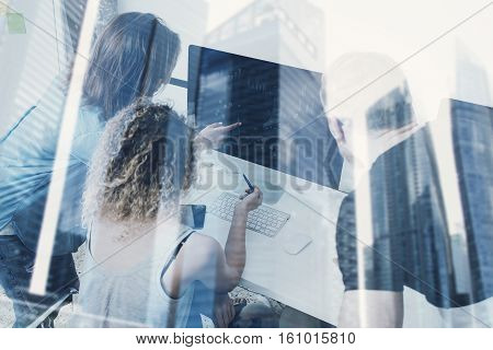 Group of young people working on computer in modern coworking studio.Coworkers using electronics gadgets.Icons, graphs and diagramm monitor.Double exposure, skyscraper building, blurred background