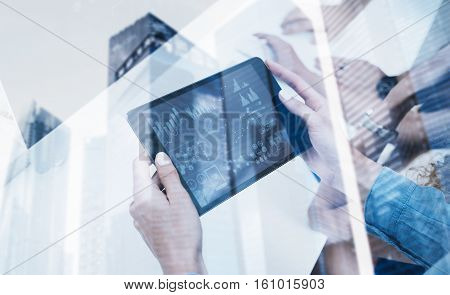 Closeup of female hands holding modern electronic tablet.Concept business people using mobile gadgets.Icon and diagramm on the display.Double exposure, skyscraper office building blurred background