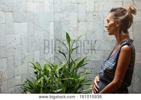 Profile Of Beautiful Pregnant Woman Wearing Summer Dress Having Rest, Standing In Front Of Big Green