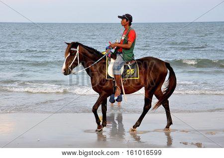 Hua Hin Thailand - December 29 2009: Thai man rides his horse along Hua Hin Beach seeking customers for a tourist ride by the sea