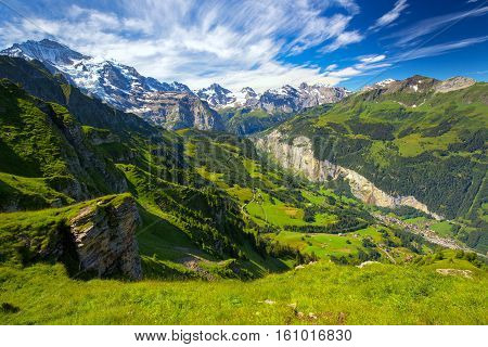 Famous Lauterbrunnen valley with gorgeous waterfall and Swiss Alps in the background from Mannlichen Berner Oberland Switzerland Europe.