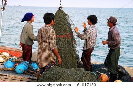 Hua Hin Thailand - January 1 2010: Thai fishermen standing on their boat repairing large fishing nets while docked at the Hua Hin public fishing pier *