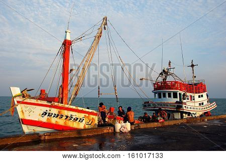 Hua Hin Thailand - January 1 2010: Thai fishing vessels and crew members relaxing while docked at the Hua Hin public fishing pier after a day at sea *