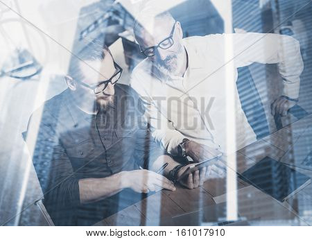 Double exposure concept.Team of business people making great time brake during work process.Young bearded man and adult businessman watching tablet.Skyscraper office building on blurred background
