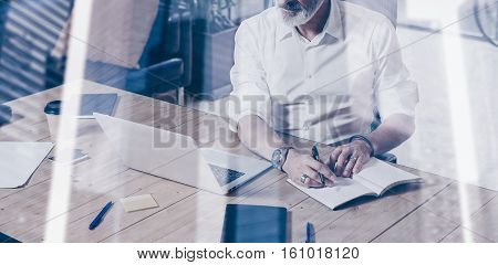 Concept of adult successful businessman wearing a classic glasses and working at the wood table in modern coworking place.Double exposure, skyscraper office building blurred background.Horizontal wide