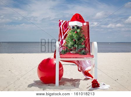 horizontal image of  little decorated Christmas tree wearing Santa Hat and sunglasses sitting in a red lawn chair on a sandy beach with the ocean behind it on  sunny summer day.