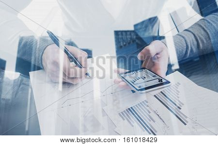 Young man working with modern smartphone in coworking place.Concept of business people using mobile gadget.Icon and diagramm on a screen.Double exposure, skyscraper office building blurred background