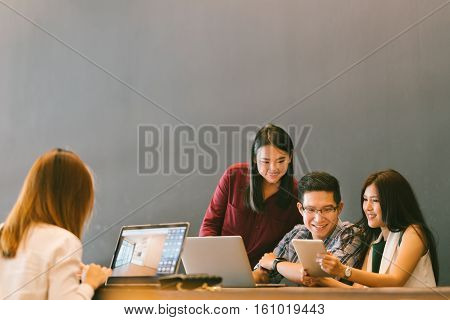 Group of young Asian business colleagues in team casual discussion, startup project business meeting or happy teamwork brainstorm concept, with copy space, depth of field effect