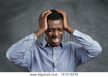Stressed African Businessman Having Bad Headache, Squeezing His Head, Closing Eyes And Clenching Tee